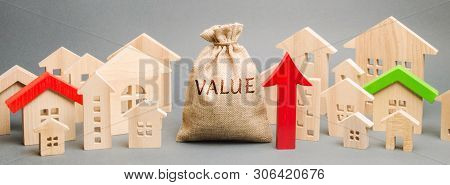 A Money Bag With The Word Value, Wooden Houses And An Up Arrow. Concept Of Real Estate Market Growth