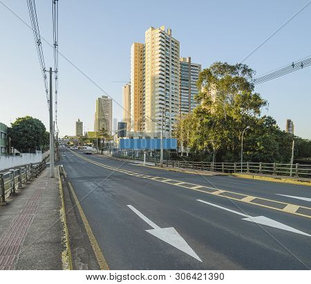 Brazilian Large Avenue With Directional Arrows On The Street. Electric Poles And Few Buildings On Ba