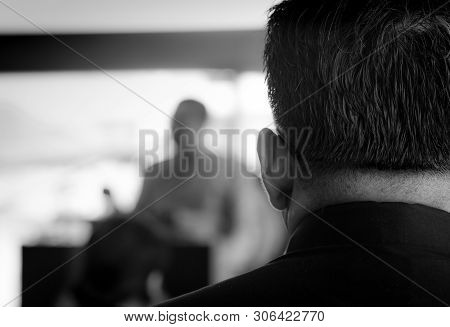 Back View Of A Man Wearing A Black Dress, Listening To The Monk Preaching At The Funeral. Funeral In