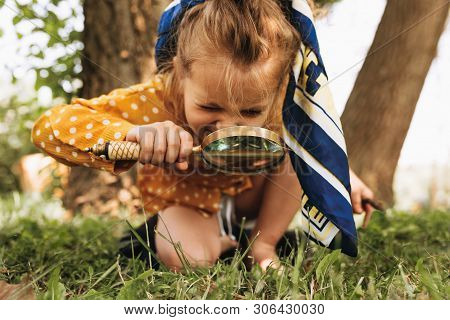 Image Of Cute Kid With Magnifying Glass Exploring The Nature Outdoors. Adorable Little Girl Playing
