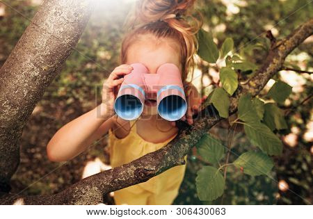 Blond Cute Little Girl Looking Through A Binoculars Searching For An Imagination Or Exploration In S