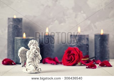 Little Angel , Rose Flower And Burning Candles On Grey Textured Background. Card For Mourning, Death