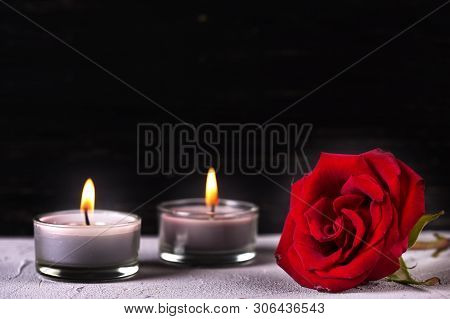 Mourning Concept. Fresh Red Rose And Burning Candles On Grey Textured Background. Card For Mourning,