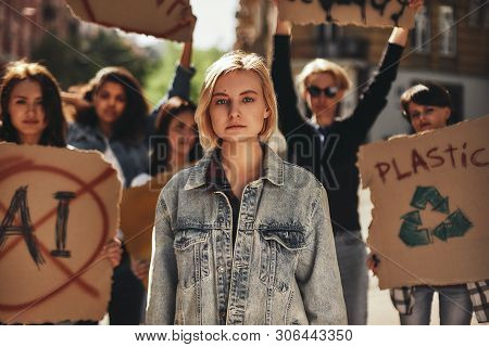 Climate Strike. Young Woman In Casual Wear Protesting With Group Of Activists Outdoors On Road