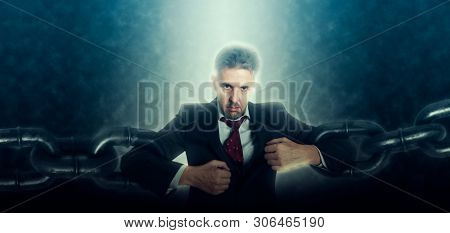 Confident and angry business man breaking chain. Business concept of liberation from credit slavery poster