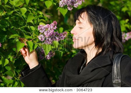 middle aged woman smelling flowers in the park/garden. poster