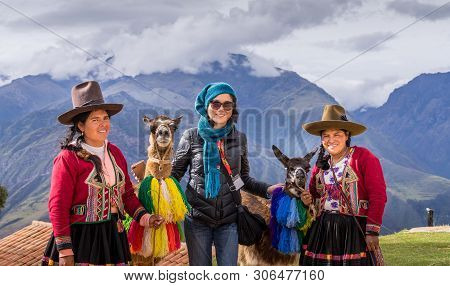 Cuzco, Peru - April 30, 2019. Peruvian Women In Traditional Clothing With Llama Picturing With Touri