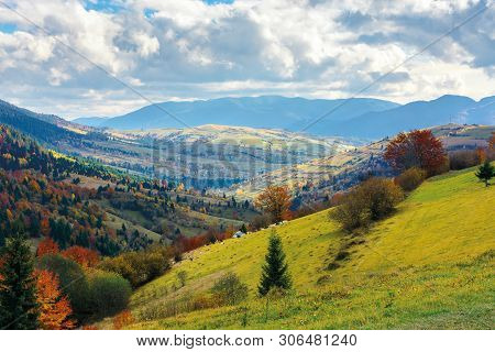 Autumn Landscape. Village On The Hillside. Forest On The Mountain Covered With Red And Yellow Leaves