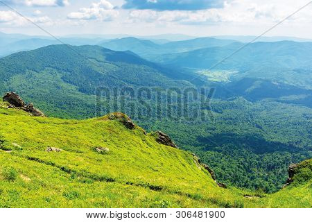 Summer Mountain Landscape. View From Steep Grassy Slope With Rock In To The Distant Valley. Sunny Af