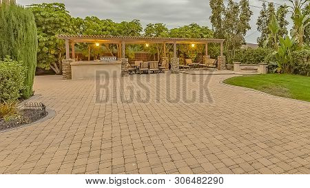 Panorama Frame Stone Brick Driveway And Patio With Fire Pit And Dining Area Under A Pavilion