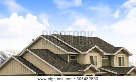 Panorama Frame House Exterior With View Of The Dark Pitched Roof Against A Cloudy Blue Sky