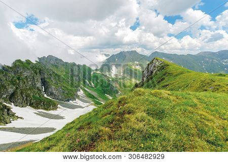 Fagaras Mountain Ridge In Summer. Spots Of Snow On Grass Of Steep Slope. Rocky Tops. Cloudy Weather.