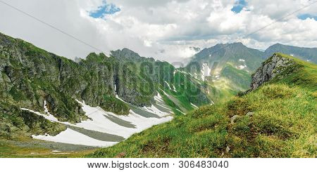 Panorama Of Fagaras Mountain Ridge In Summer. Spots Of Snow On Grass Of Steep Slope. Rocky Tops. Clo