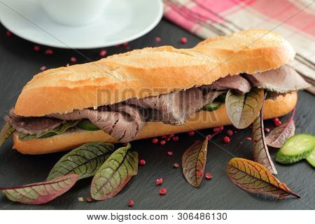 Big roast beef sandwich with red chard leaves, crusty French baguette dip