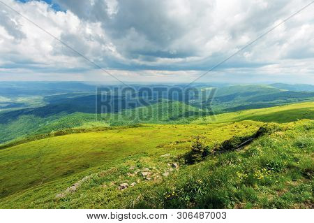 Mountain Landscape On A Cloudy Day. Footpath Through Grassy Meadow. Mountain Ridge In The Distance.