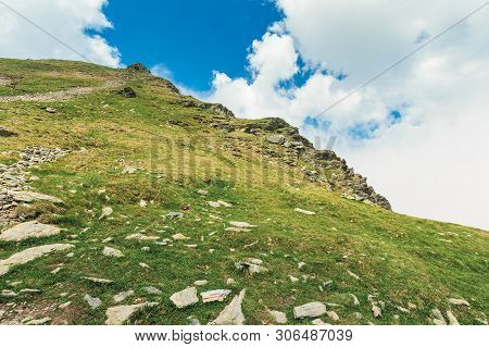Hiking Up The High Hill. Beautiful Summer Scenery With Clouds On A Blue Sky. Rocks On Grassy Slope.