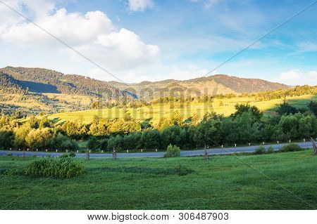 Carpathian Countryside In The Morning. Field Near The Road In Shade. Mountains And Rural Hills In Su
