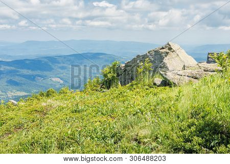 Rock On The Edge Of A Hill. Sunny Scenery In Mountains. Green Grassy Meadow And Blue Summer Sky. Idy