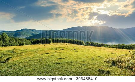 Meadow On The Hill Among The Forest. Bright Summer Scenery On A Cloudy Forenoon. Fog Start To Rise F