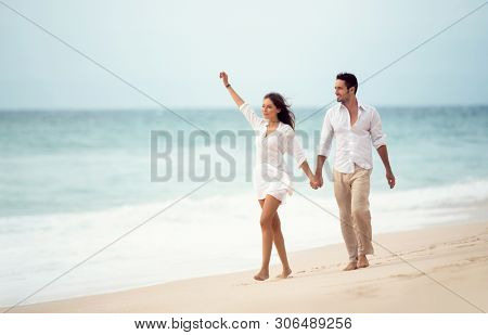 Couple walking on beach. Young happy couple walking on beach smiling holding hands