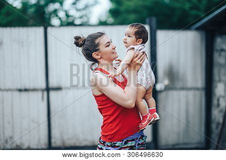 Beautiful Mother And Baby Outdoors On The Yard Of House. Beauty Mum And Her Baby Child One Year Old