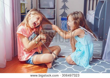 poster of Two little mad angry girls sisters having fight at home. Friends girls can not share toy bag. Lifestyle authentic funny family moment of siblings quarrel. Kids bad behaviour.