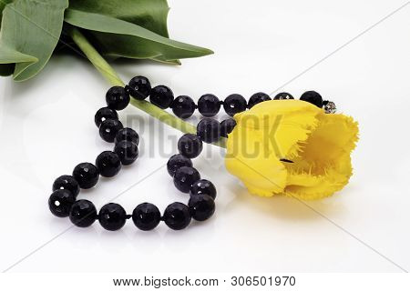 Bright Black Beads And Yellow Tulip With Green Leaves.