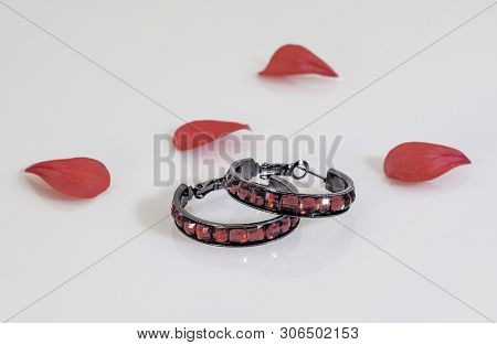 Two Dark Round Earrings With Bright Red Stones And Red Flower Petals.