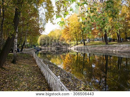 Autumn Park, Trees Reflected In The Pond, White Rusty Fence, Withered Leaves, Stone Waterfall