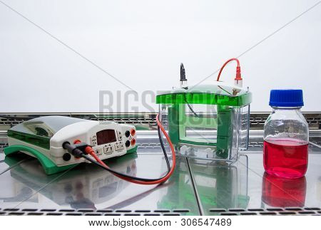 Equipment and a flask with a red liquid are placed in a glass sterile cabinet. Preparing for the experiment with the red liquid. Equipment for electrophoresis. poster