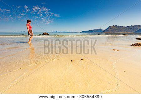 Tourist Woman Relaxing Walking On Sea Shore. Coast Of Gimsoya Island, Gimsoysand Sandy Beach In Summ