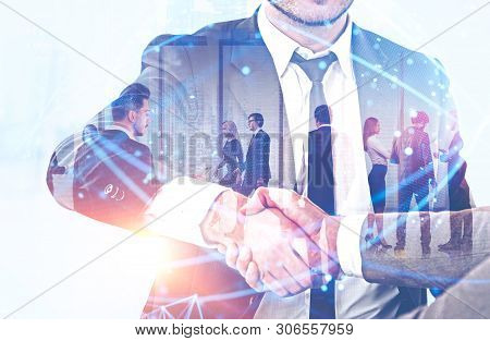 Handshake Of Business People With Double Exposure Of Their Team Working In Office. Global Digital Ne