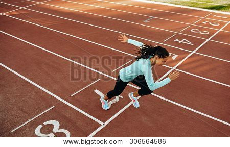 Outdoor Horizontal Image Of Young Woman Athlete Running On Racetrack At Stadium. View From Above Of