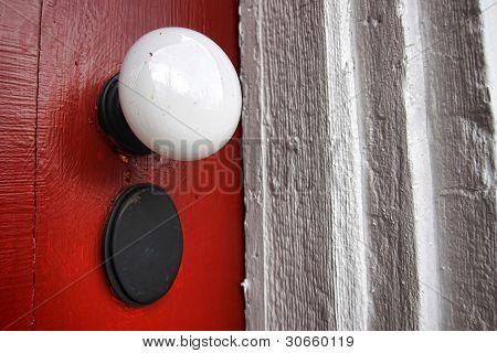 Old Doorknob On Antique Red Door Of Historic Home