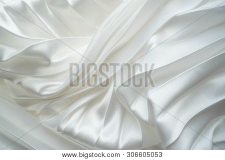 White Silk Or Satin Fabric Folded Background. Luxurious Fabric Cloth Fold Glamour Background. Tender