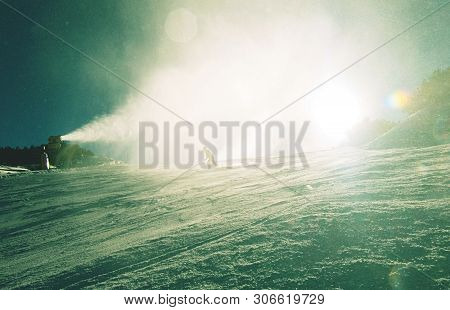 Snowboarders And Snow Cannon In Action In Winter.  Snow Cannon Against Sunlit Snow In Park City