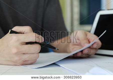 Close Up Man Writing On Paper On The Table In A Office Room. Mobile Device Placed Beside. Doing Pape