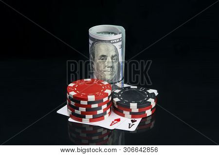 Two Stacks Of Colored Chips, For Playing In The Casino, Next To A Roll Of Dollars, On A Black Backgr