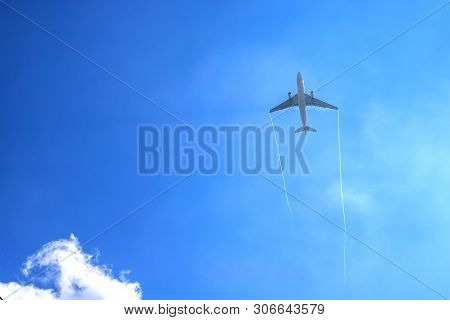 Airplan Leaves A Trail In The Blue Sky . Airliner Is Takking Off. White Cloud In The Blue Sky In Whi