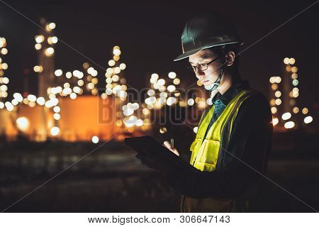 Asian Man Engineer Using Digital Tablet Working Late Night Shift At Petroleum Oil Refinery In Indust