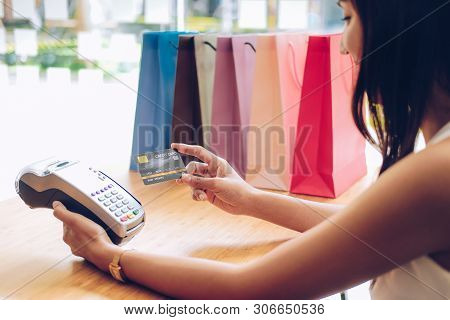 Woman Using Credit Card Swiping Machine With Shopping Bags On Table. Payment With Nfc Technology