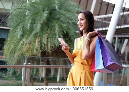 Woman Holding Smartphone & Shopping Bags. Consumerism Lifestyle In Mall