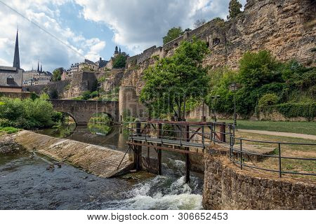 Weir In Alzette River Luxembourg City Downtown Grund With Medieval Fortifications And Old Stonebridg