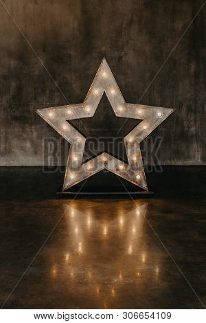 Interior In A Fashionable Loft Style. Decorative Star With Lamps On A Wall Background. Glamour Photo