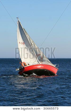 Sailboat sailing in the morning at a deep blue sea