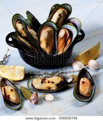Boiled Green Mussels With Herbs, Garlic And Lemon In Blue Pannikin Closeup On Blue Wooden Background