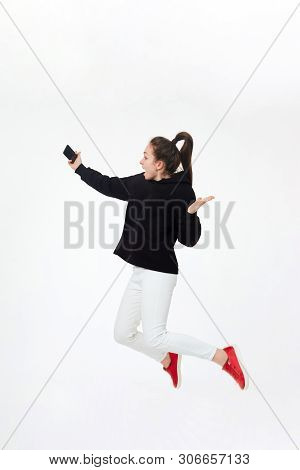 Young Pretty Brunette Girl In Black Hoodie, White Pants And Red Sneakers Making Selfie With Mobile P