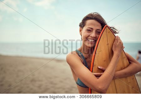 Smiling surfer girl posing with her surfboard on the beach.