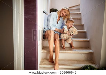 Mother with cute child sitting on the stairs