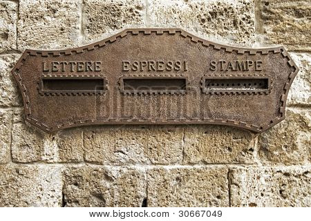 Vintage rusty iron mail box on stone wall at Venice, in Italy
